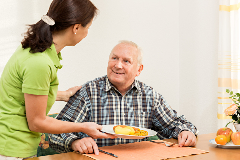 Caregiver giving senior man lunch in the kitchen