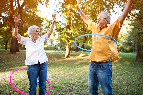 Happy funny senior couple playing hulahoop in park