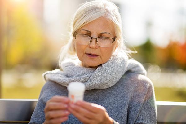 Senior woman checking label on medication