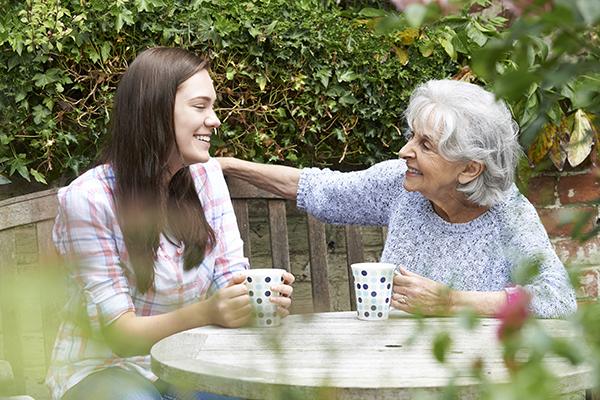 Granddaughter Relaxing With Grandmother In Garden