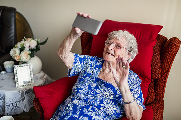 An elderly woman is using a smartphone.
