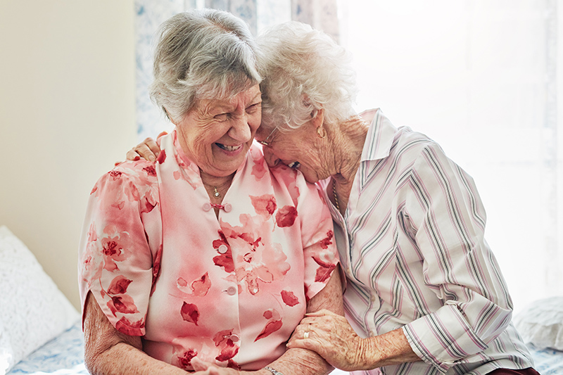 two happy elderly women spending time with each other at home