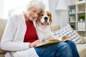 happy senior woman reading with dog