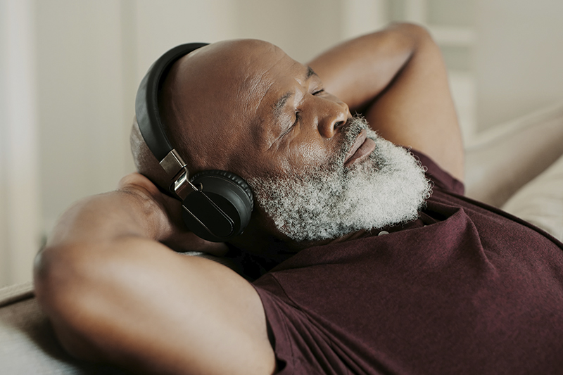 man relaxing listing to headphones