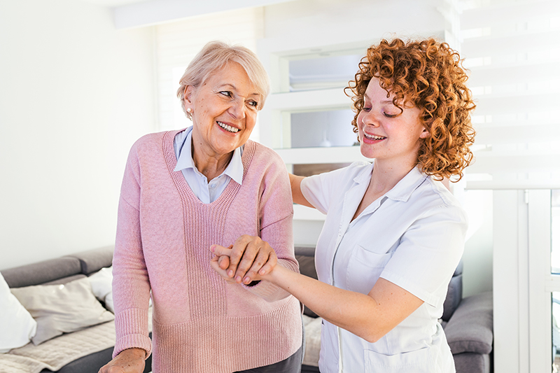 senior woman receiving assistance from caregiver