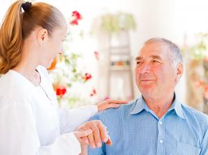 caregiver assisting senior man with Parkinson's