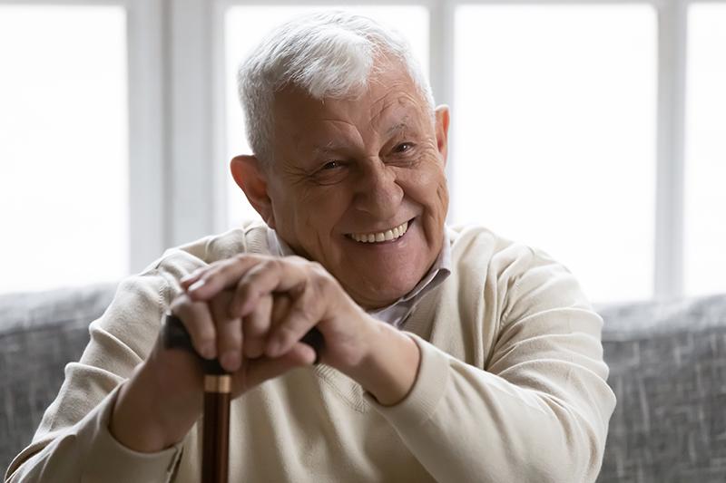 Happy senior safety leaning on cane